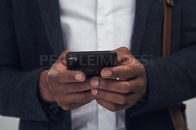 Buy stock photo Studio shot of an unrecognisable businessman using a smartphone against a grey background
