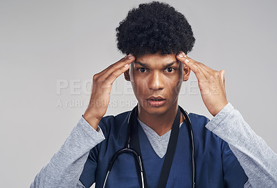 Buy stock photo Shot of a male nurse looking frustrated while standing against a grey background