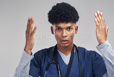 Buy stock photo Shot of a male nurse looking confused while standing against a grey background