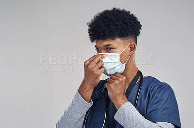 Buy stock photo Shot of a male nurse wearing a surgical mask while standing against a grey background