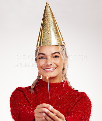 Buy stock photo Studio shot of a young woman wearing a party hat while holding a sparkler against a grey background