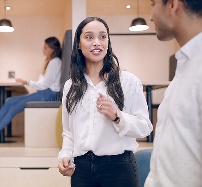 Buy stock photo Shot of an attractive young businesswoman standing in the office and having a discussion with a colleague