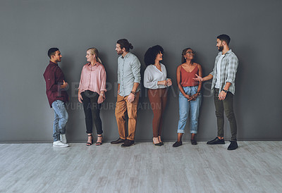 Buy stock photo Studio shot of a diverse group of people talking to each other against a grey background