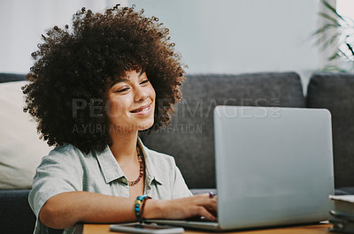 Buy stock photo Shot of an attractive young woman sitting on the floor in her living room and using her laptop