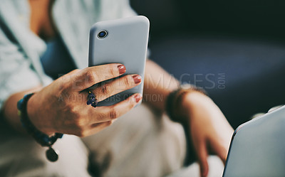 Buy stock photo Cropped shot of an unrecognisable woman sitting alone on her sofa at home while using her laptop and cellphone