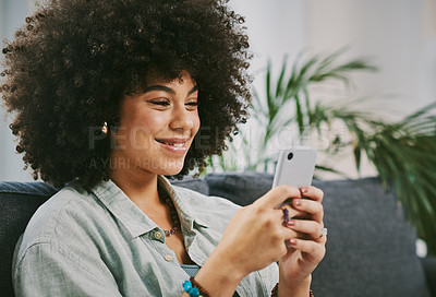 Buy stock photo Shot of an attractive young woman sitting alone on her sofa at home and using her cellphone