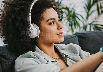 Buy stock photo Shot of an attractive young woman sitting alone on her sofa at home and listening to music through headphones