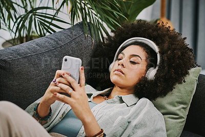 Buy stock photo Shot of an attractive young woman lying on her sofa and listening to music through headphones while using her cellphone