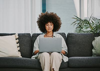 Buy stock photo Shot of an attractive young woman sitting alone on her sofa at home and using her laptop