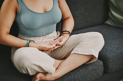 Buy stock photo Cropped shot of an unrecognisable woman sitting alone on her sofa at home and meditating