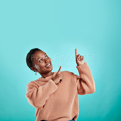 Buy stock photo Shot of a young woman pointing up while standing against a turquoise background