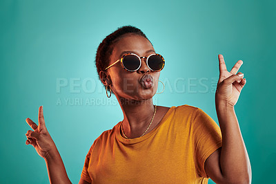 Buy stock photo Shot of a woman wearing sunglasses and showing the peace sign