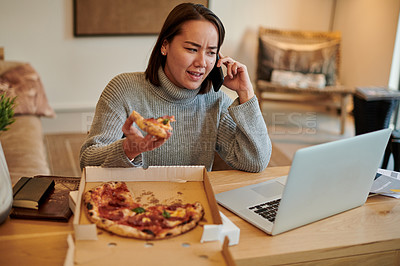 Buy stock photo Shot of a young woman enjoying some pizza while using her smartphone to make a phone call