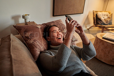 Buy stock photo Shot of a young woman relaxing on her sofa using her smartphone to send text messages