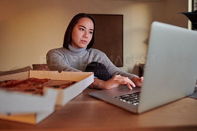 Buy stock photo Shot of a young woman working from home while eating pizza