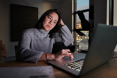Buy stock photo Shot of a young businesswoman taking a break from work to use her smartphone