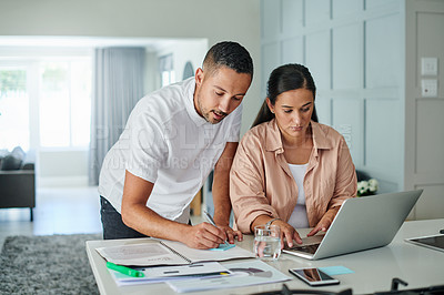 Buy stock photo Shot of a young couple reading paperwork and using a laptop to work from home