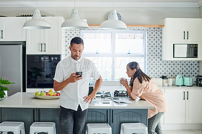 Buy stock photo Shot of a handsome young man standing in his kitchen and using his cellphone while his wife drinks coffee