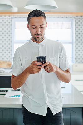 Buy stock photo Shot of a handsome young man standing alone in his kitchen and using his cellphone