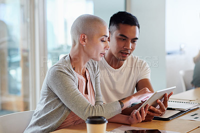 Buy stock photo Cropped shot of two young businesspeople looking over a tablet while sitting in the boardroom