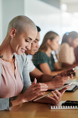 Buy stock photo Cropped shot of an attractive young businesswoman using her tablet while sitting in the boardroom with her colleagues