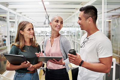 Buy stock photo Cropped shot of three young businesspeople having an impromptu meeting in their office corridor