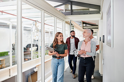 Buy stock photo Cropped shot of a group of young businesspeople walking through the corridor of their creative office