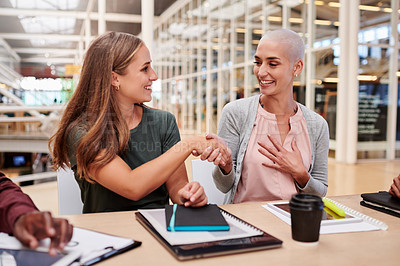 Buy stock photo Cropped shot of two attractive young businesswomen shaking hands during a meeting in their office boardroom