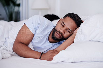 Buy stock photo Shot of a handsome young man lying in bed at home and looking upset while his girlfriend sleeps behind him