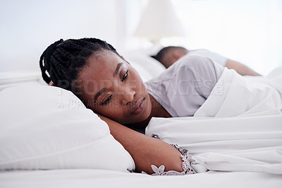 Buy stock photo Shot of an attractive young woman lying in bed at home and looking upset while her boyfriend sleeps behind her