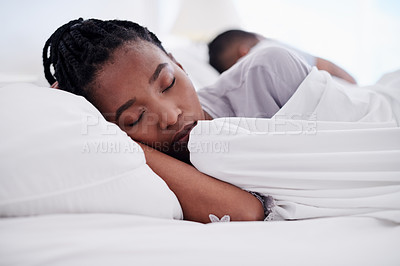Buy stock photo Shot of an attractive young woman sleeping in her bed at home while her boyfriend lies behind her