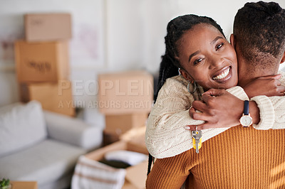 Buy stock photo Shot of a young couple hugging while showing their new house keys at home