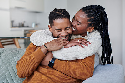 Buy stock photo Shot of a young woman biting her boyfriend's ear while relaxing together at home