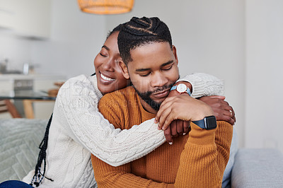 Buy stock photo Shot of an affectionate young couple hugging each other at home
