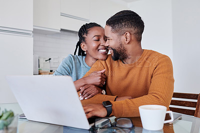 Buy stock photo Shot of a young couple using a laptop while having coffee together at home