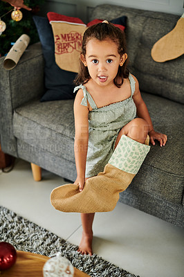 Buy stock photo High angle portrait of an adorable little girl trying to wear a Christmas stocking as a sock while sitting on a sofa at home