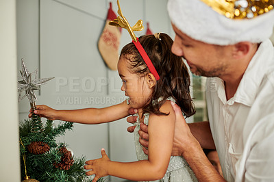 Buy stock photo Cropped shot of an adorable little girl putting the star on top of her family Christmas with a little help from dad