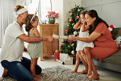 Buy stock photo Full length shot of an affectionate young family popping Christmas crackers in their living room at home