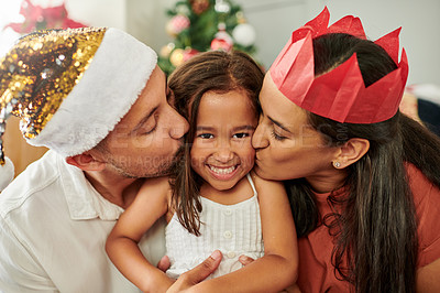 Buy stock photo Cropped portrait of an adorable little girl being kissed on each cheek by her mother and father at home on Christmas eve