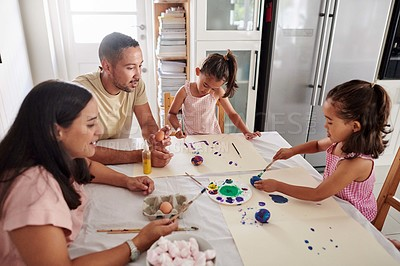 Buy stock photo Shot of a mother and father painting eggs with their daughter at home
