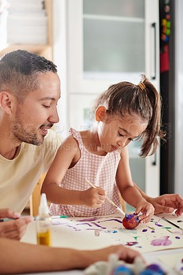 Buy stock photo Shot of a man painting eggs with his daughter at home