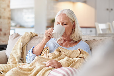 Buy stock photo Shot of a senior woman drinking tea while feeling sick at home