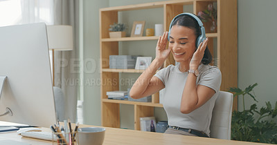 Buy stock photo Shot of a young woman wearing headphones while using a computer at home