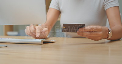 Buy stock photo Shot of an unrecognizable person holding a credit card while using a computer at home