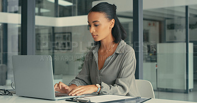 Buy stock photo Shot of a young woman using her laptop in a modern office