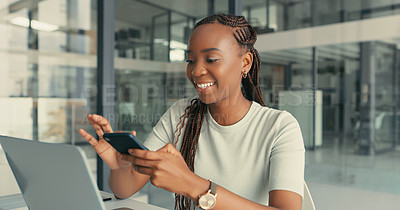 Buy stock photo Shot of a young woman using her cellphone in a modern while working on her laptop in a modern office