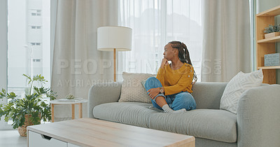Buy stock photo Shot of a young woman sitting on a couch at home