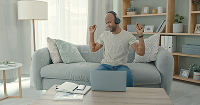 Buy stock photo Shot of a young man using a laptop while wearing headphones at home