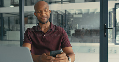 Buy stock photo Shot of a young man using his cellphone while working on his laptop in a modern office