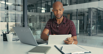 Buy stock photo Shot of a young man using his digital tablet and laptop to get his work done in a modern office